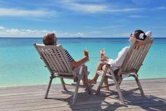 Le giovani coppie felici si rilassano e prendono la bevanda fresca fotografie stock libere da diritti