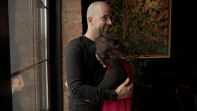 Le giovani coppie felici stanno vicino alla finestra panoramica nel caffè video d archivio