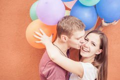 Le giovani coppie felici vicino alla parete arancio stanno con i palloni Fotografia Stock