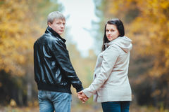 Le giovani coppie incinte amorose che camminano in autunno parcheggiano Fotografie Stock