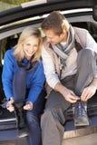 Le giovani coppie legano i caricamenti del sistema alla parte posteriore dell'automobile Fotografia Stock