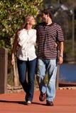 Le giovani coppie nell'amore camminano da un lago Immagine Stock