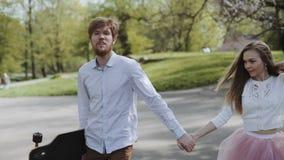 Le giovani coppie nell'amore che cammina di estate parcheggiano tenersi per mano Donna nell'uomo rosa della gonna del tutu con il video d archivio