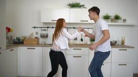 Le giovani coppie recentemente wed nel dancing felice di amore che ascolta la musica nella mattina d'uso dei pigiami della cucina stock footage