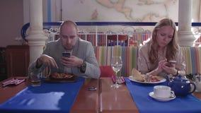Le giovani coppie in ristorante attaccato in loro telefoni e si trascurano archivi video