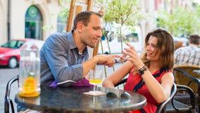 Le giovani coppie si divertono in caffè con il telefono cellulare. Fotografia Stock