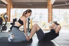 Le giovani coppie si esercitano insieme nello stile di vita sano della palestra Immagini Stock