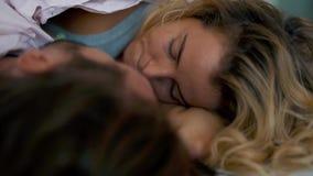 Le giovani coppie si guardano negli occhi sul letto stock footage