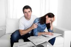 Le giovani coppie si sono preoccupate a casa nel marito di sforzo che conforta la moglie nei problemi finanziari fotografia stock