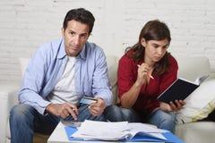 Le giovani coppie si sono preoccupate e disperato sui problemi dei soldi a casa nei pagamenti della banca di contabilità di sforz Fotografia Stock Libera da Diritti