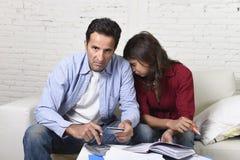 Le giovani coppie si sono preoccupate e disperato sui problemi dei soldi a casa nei pagamenti della banca di contabilità di sforz Fotografia Stock