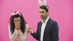 Le giovani coppie sono belle su fondo rosa Durante questo tempo sono vestiti in orecchie della ressa Isolato su bianco in studio video d archivio