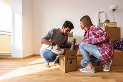 Le giovani coppie sono entrato appena nel nuovo appartamento vuoto che disimballa e che pulisce - la rilocazione fotografia stock libera da diritti