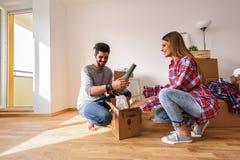 Le giovani coppie sono entrato appena nel nuovo appartamento vuoto che disimballa e che pulisce - la rilocazione immagine stock libera da diritti