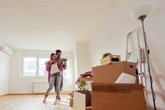 Le giovani coppie sono entrato appena nel nuovo appartamento vuoto che disimballa e che pulisce - la rilocazione fotografie stock