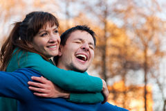 Le giovani coppie sorridenti che stanno in autunno parcheggiano Fotografia Stock