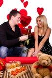 Le giovani coppie sorridenti felici con sono aumentato Fotografie Stock Libere da Diritti