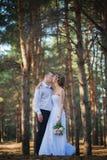 Le giovani coppie sposate allegre stanno baciando Fotografie Stock