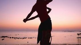 Le giovani coppie stanno su un'oscillazione che si tiene per mano alla spiaggia tropicale contro il mare durante il tramonto sbal video d archivio