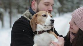 Le giovani coppie sveglie dei pantaloni a vita bassa che si divertono nell'inverno parcheggiano con il loro cane un giorno e sorr archivi video