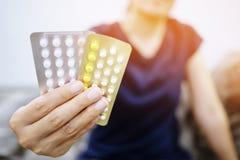 Le giovani donne alte vicine passano la pillola anticoncezionale sopra con le strisce variopinte delle pillole immagini stock libere da diritti