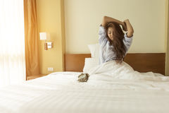 Le giovani donne asiatiche svegliano ed allungando mentre si siedono nell' Fotografia Stock Libera da Diritti