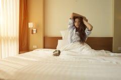 Le giovani donne asiatiche svegliano ed allungando mentre si siedono nell' Fotografie Stock Libere da Diritti