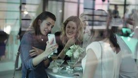 Le giovani donne attraenti stanno avendo buon tempo intorno alla tavola al terrazzo aperto archivi video