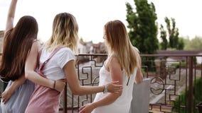 Le giovani donne ballano felicemente sul balcone Movimenti spensierati Vestiti moderni e alla moda Ridendo ed avendo divertimento video d archivio