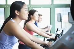 Le giovani donne che si esercitano sulla forma fisica bikes nella palestra Immagine Stock