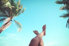 Le giovani donne che si trovano su una spiaggia tropicale, si rilassano l'allungamento sulle gambe snelle abbronzate Fotografia Stock Libera da Diritti