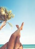 Le giovani donne che si trovano su una spiaggia tropicale, si rilassano l'allungamento sulle gambe snelle abbronzate Immagini Stock