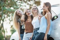 Le giovani donne che stanno vicino all'automobile Immagine Stock