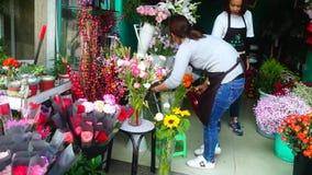 Le giovani donne cinesi azionano i negozi di fiore stock footage