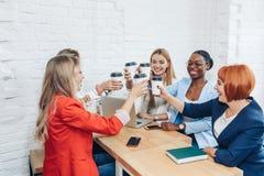 Le giovani donne collaborano con gli amici indipendenti e creano un piccolo club coworking fotografia stock