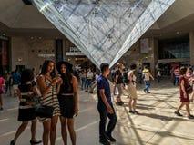 Le giovani donne controllano i colpi del selfie davanti alla piramide capovolta in carosello del Louvre fotografia stock libera da diritti