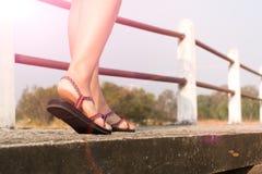 Le giovani donne del viaggiatore sulle scarpe da tennis calzano la camminata sul ponte sulle giovani donne dello straveler sulla  Fotografia Stock