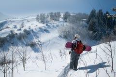Le giovani donne dello snowboarder sta andando per il freeride ad in salita Fotografia Stock