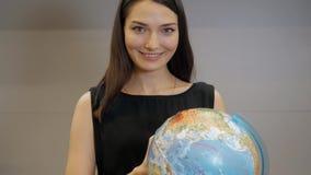 Le giovani donne di affari sorridenti con il globo, donna castana felice scelgono il viaggio Fotografie Stock