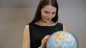 Le giovani donne di affari sorridenti con il globo, donna castana felice scelgono il viaggio Fotografie Stock Libere da Diritti