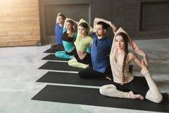 Le giovani donne e gli uomini nell'yoga classificano, allungamento di posa della sirena Fotografia Stock Libera da Diritti