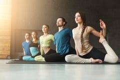 Le giovani donne e gli uomini nell'yoga classificano, allungamento di posa della sirena Immagini Stock