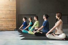 Le giovani donne e gli uomini nell'yoga classificano, si rilassano la posa di meditazione Fotografia Stock Libera da Diritti