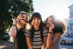 Le giovani donne fanno i fronti con i baffi fatti di capelli fotografia stock