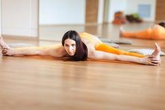 Le giovani donne graziose in sport arancio sono adatto a fare l'allungamento prima della pratica dell'yoga sul pavimento in una s Immagine Stock Libera da Diritti