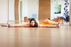 Le giovani donne graziose in sport arancio sono adatto a fare l'allungamento prima della pratica dell'yoga sul pavimento in una s Fotografia Stock