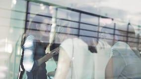 Le giovani donne graziose stanno avendo buon tempo intorno alla tavola al terrazzo aperto video d archivio