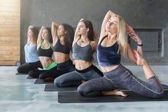 Le giovani donne nell'yoga classificano, allungamento di posa della sirena Immagini Stock