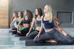 Le giovani donne nell'yoga classificano, allungamento di posa della sirena Immagini Stock Libere da Diritti