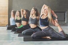 Le giovani donne nell'yoga classificano, allungamento di posa della sirena Immagine Stock Libera da Diritti